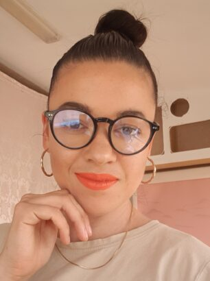 Image of Esme smiling and wearing orange lipstick and blue-light blocking glasses.